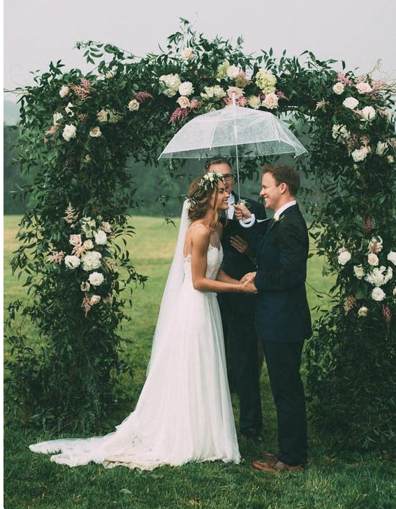 Bride and Groom holding an umbrella getting married outside in the rain